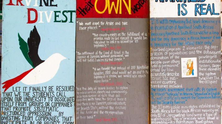 Three painted signs explain why people should participate in the Boycott, Divest and Sanctions movement against Israel