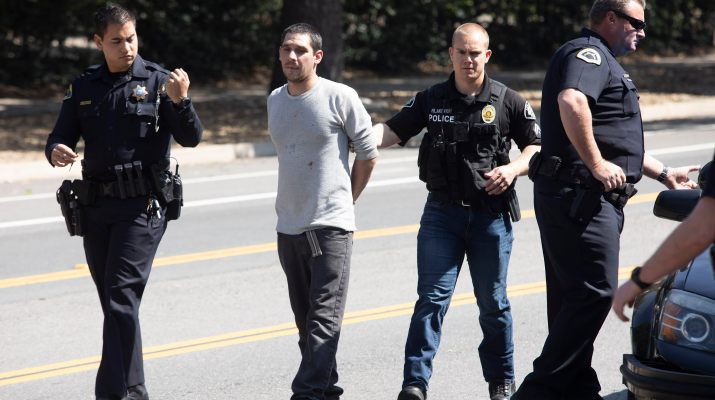 Three police officers escort a man in handcuffs.