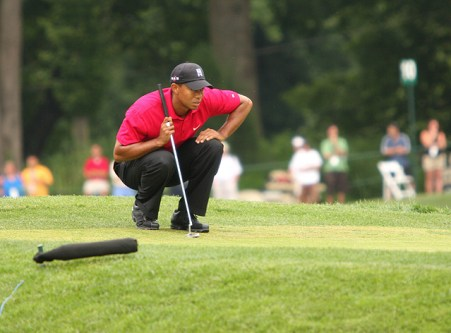 Tiger Woods crouching down and reading a putt on the green at a golf tournament.