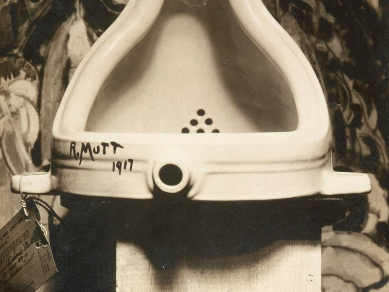 """A photo of Duchamp's """"Fountain,"""" a urinal with """"R. Mutt 1917"""" written on it."""