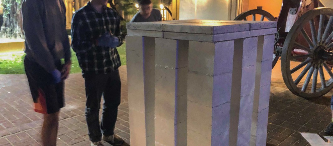 A photograph of three Harvey Mudd College students looking at the finished gray concrete structure (without the plaque attached) at Caltech during the night. (Jaimie Ding • The Student Life)