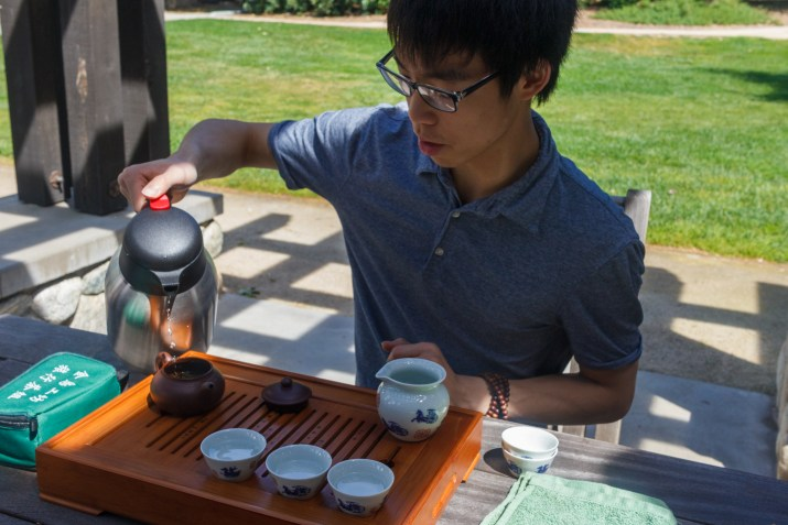 A photograph of Andrew Nguy PO '19 pouring water into a small brown teapot. He is wearing a blue shirt and sitting behind a table.
