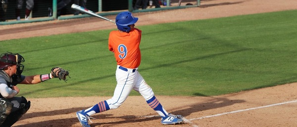 A baseball player with a blue helmet, orange jersey, and white pants swings his bat while a catcher squats behind him with the ball in his glove.