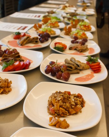 "A picture of several cricket-based dishes lining the table. In front is the apple ""Crispckt"" dish made by Team Pomona, and behind is a plate of lemon poppy cricket pancakes."