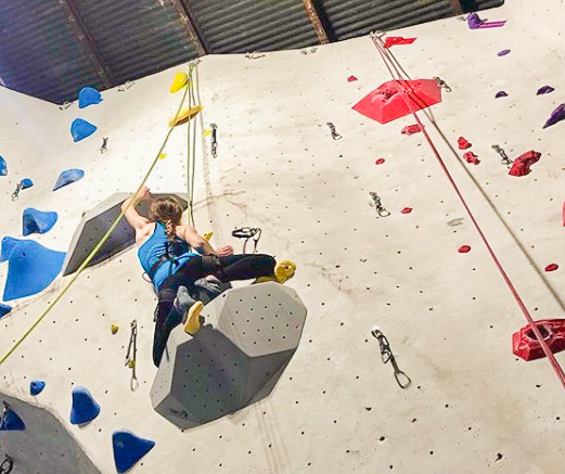 A woman is photgraphed from 10 feet below, climbing a rock wall. She is wearing black leggings and a blue tank top, her shoulder muscles are flexing!
