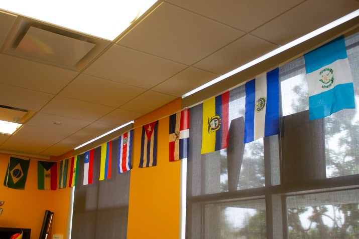 A string of colorful flags hangs across the top edge of a classroom. The flags are from Central and South America countries such as Guatemala, El Salvador, Ecuador, and others.