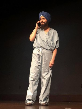 Sundeep Morrison in performance. She is playing a male character, and is wearing a gray medical uniform and a navy turban. The character has a mustache and a beard, and is standing while on the phone.