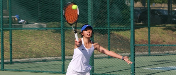 A tennis player hits the ball with the racquet in her right hand, left arm outstretched.