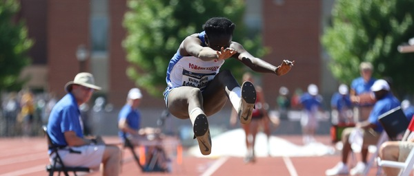 A jumper competes in the long jump, airborn with her feet and hands all outstretched towards the camera.