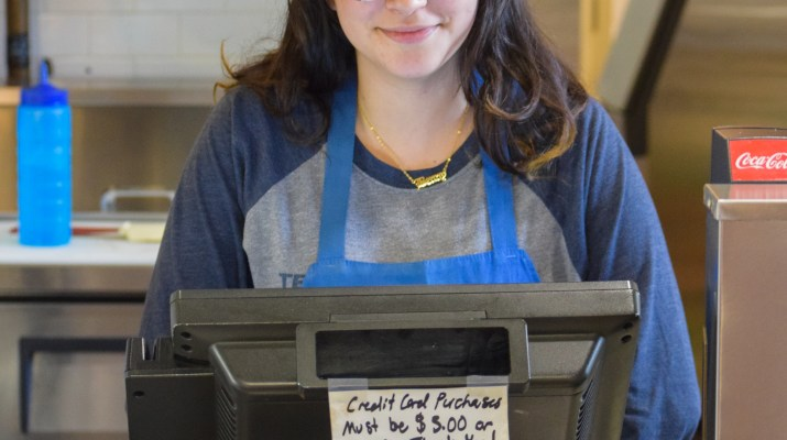 A woman, Diana Rodriguez, stands behind a cash register wearing an apron.