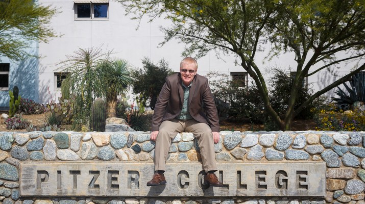 NIgel sits on cobble wall that says pitzer college. he looks very happy and is wearing a brown suit.