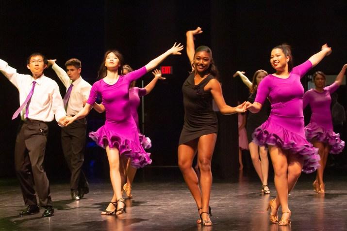 Four student dancers on stage. Simon Chen PO '22 (left) wears a white shirt, black pants a purple tie. Ashley Chen PO '22 (second from left) wears a purple dress. Rachel Hall PO '22 (second from right) wears a black dress. Lucie Wharton-Moeur SC '21 wears a purple dress.