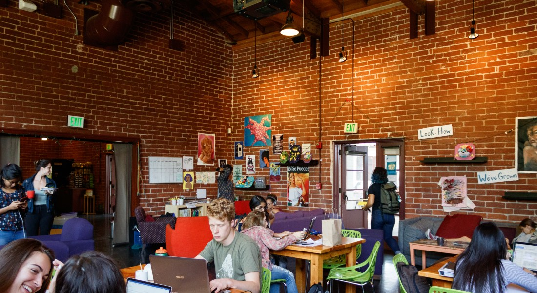 students study in the motley, sitting on couches. The walls are brick