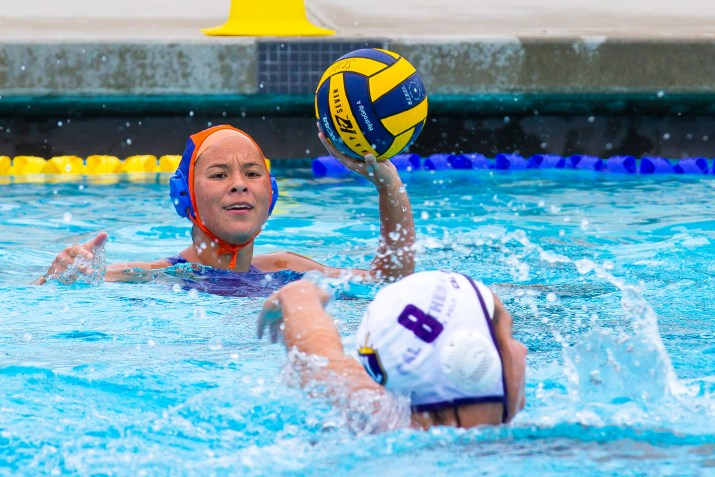Natalie Hill holds the ball aloft, scanning the pool for a path of attack.