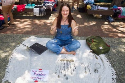 Maya Cohrssen-Hernández SC '21 sits cross-legged on top of a white blanket. She is wearing denim overalls, and several necklaces are on display in front of her.