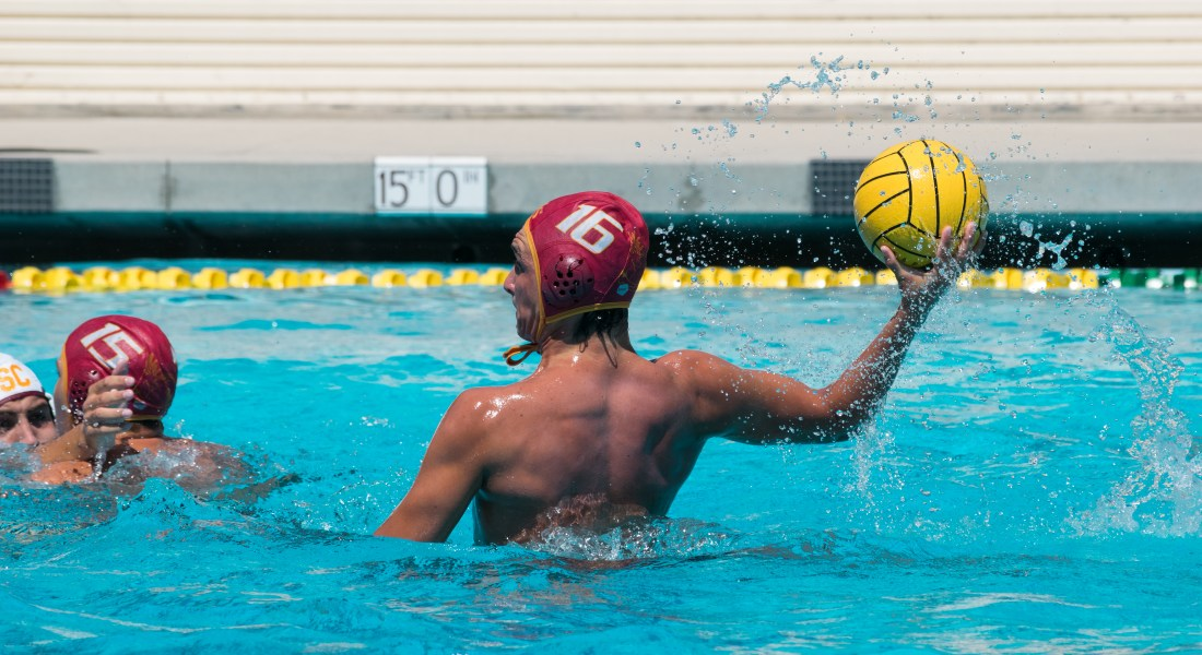 A water polo player rises above the water and prepares to throw a ball.