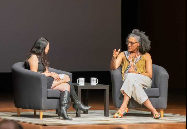 Carla Hall responds to questions from Rachel Ng from a blue armchair on a stage.