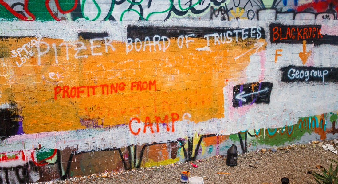 """A brick wall has been spray painted with the words """"Pitzer Board of Trustees,"""" """"BlackRock,"""" """"GEO Group,"""" and """"profiting from camps."""""""