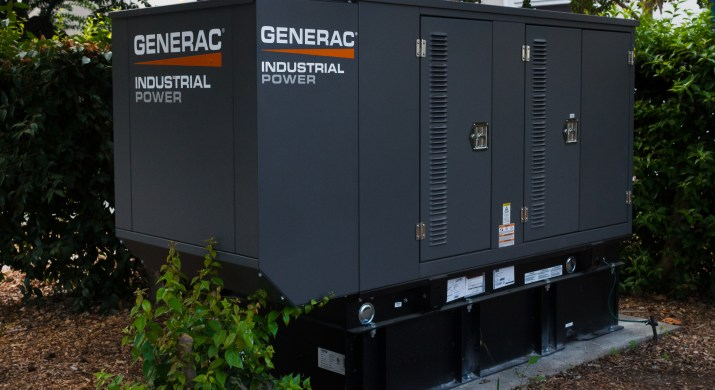 """A outdoor grey generator with the brand name """"Generac"""" written across it sits in between some bushes."""