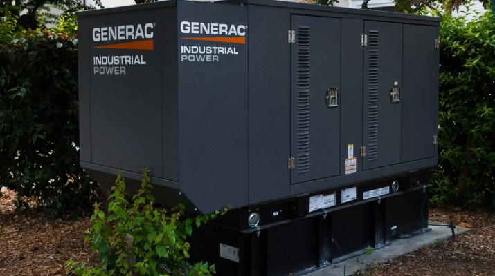 "A outdoor grey generator with the brand name ""Generac"" written across it sits in between some bushes."