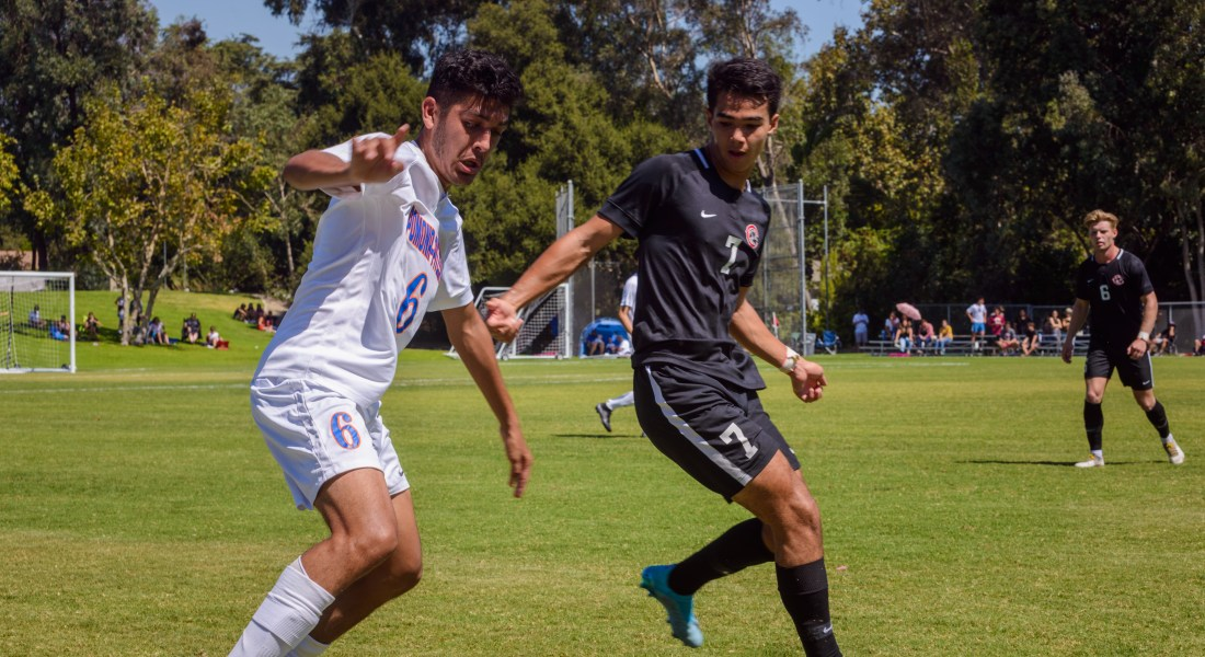 A male soccer player in white kicks the ball while another male athlete in black tries to guard him.