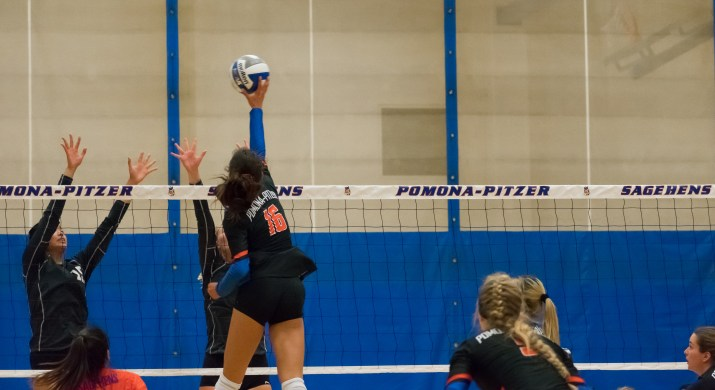A female volleyball player spikes the ball over the net.