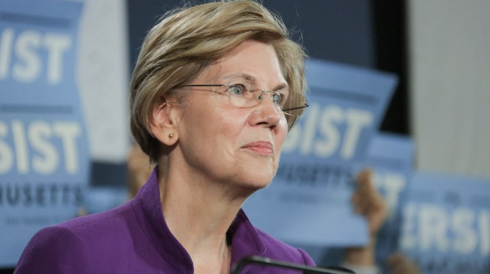 Elizabeth Warren smiling in front of many blue signs