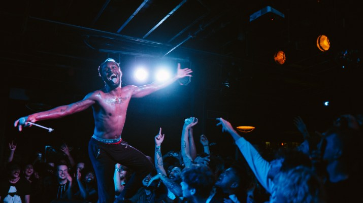 A shirtless man with a microphone smiles above a crowd in a dark room.