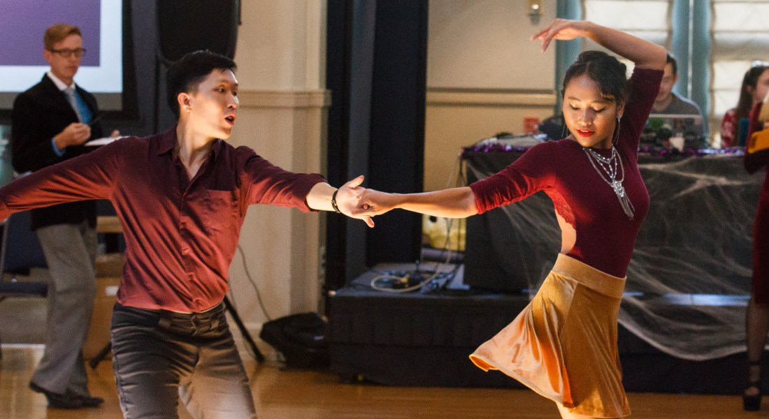 A male college student in maroon and black spins his female dance partner who is wearing a maroon top and gold skirt.