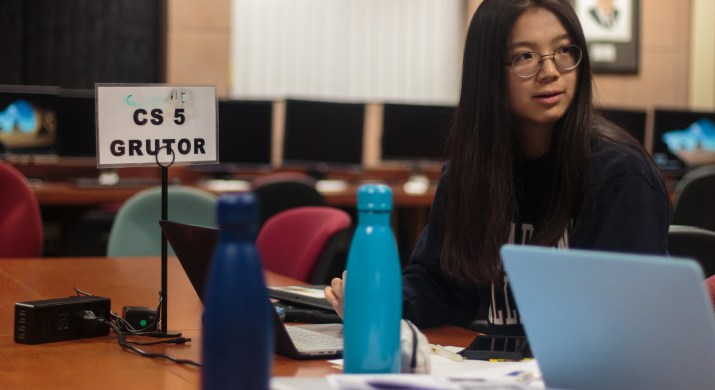 """A female college student sits at a desk, working at her computer. A sign next to her reads """"CS 5 Grutor."""""""