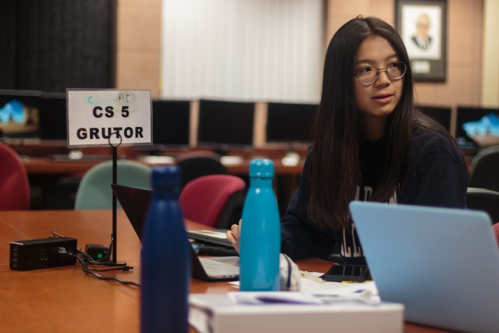"A female college student sits at a desk, working at her computer. A sign next to her reads ""CS 5 Grutor."""