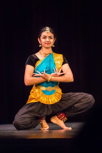 A female college student in traditional Indian classical attire holds a pose during a dance.