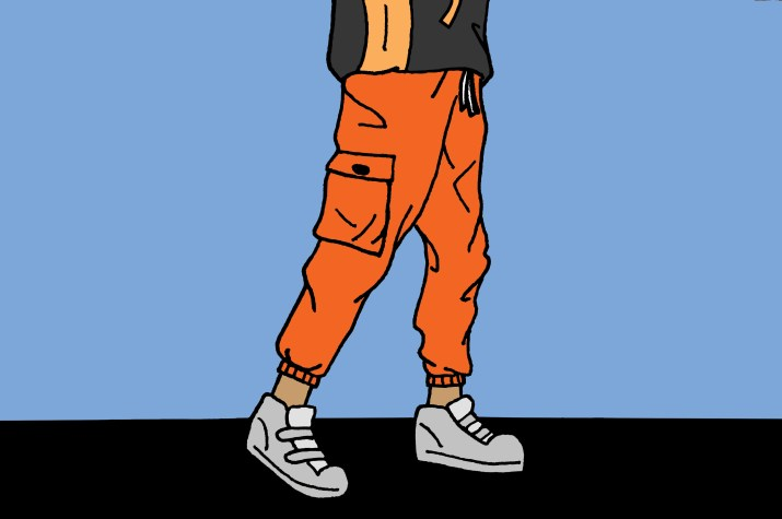 An image of a person from the waist down wearing orange baggy pants and gray sneakers.
