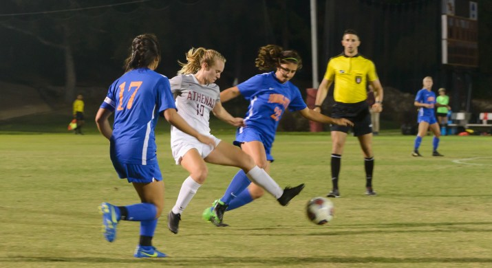 A female athlete in white moves between two athletes in blue during a nighttime soccer game.