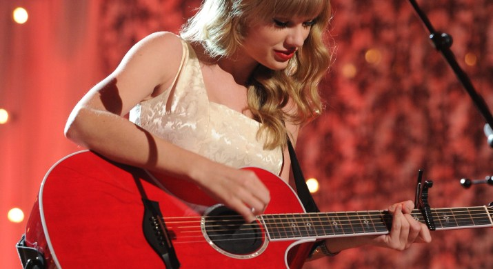 Taylor Swift stands on stage, holding a red guitar and singing.