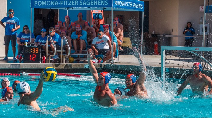 A male water polo player takes a shot on goal while opposing players defend the goal.