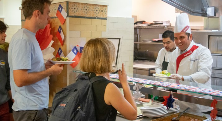 A male chef with a tall white hat prepares to hand a plate of food to a female student from behind a counter.