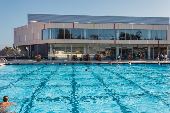 People swim in an olympic-sized pool next to a large modern facility with large windows.