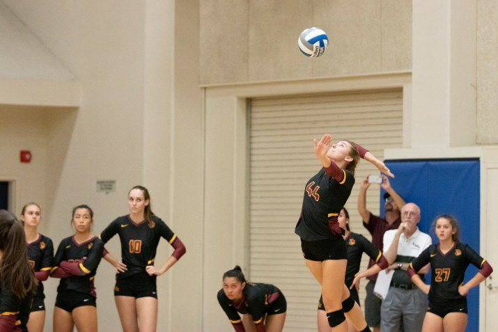 A girl in a yellow, black, and red uniform throws a volleyball in the air in order to serve the ball.