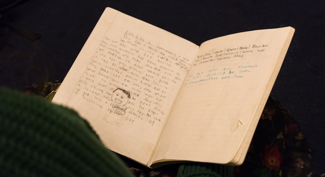 A student holds a notebook in their lap. The notebook displays a children's creative writing story with some doodles.