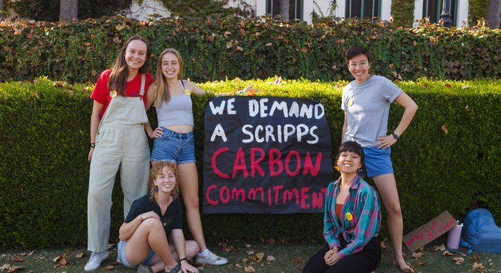 """Five female college students stand around a sign that reads """"We Demand A Scripps Carbon Commitment."""""""