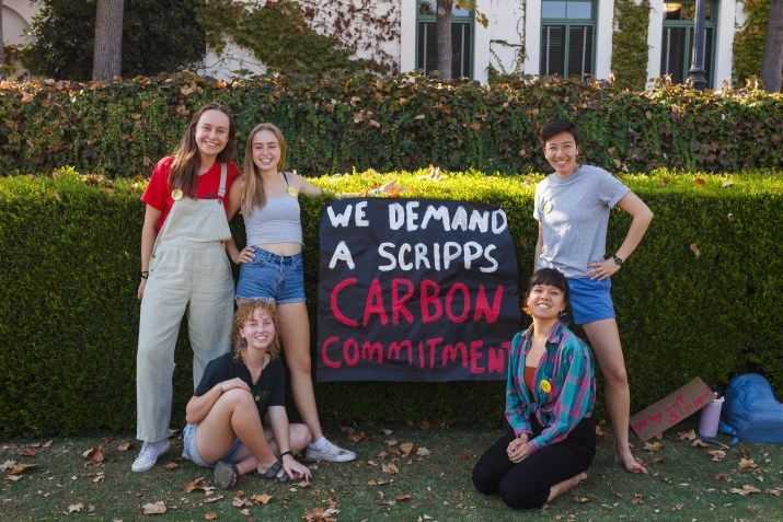 "Five female college students stand around a sign that reads ""We Demand A Scripps Carbon Commitment."""