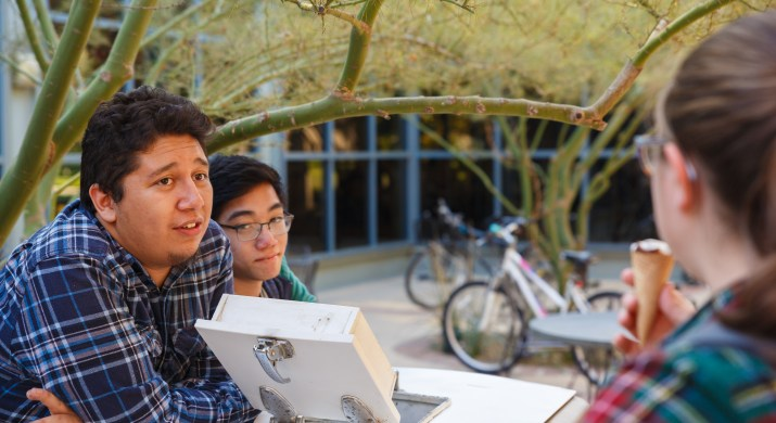 Two male college students stand behind a small ice cream freezer in front of Harvey Mudd's dining hall, while a female student eats ice cream in the foreground