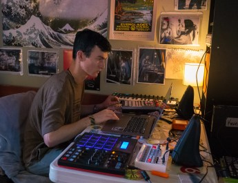 White male college student sits at a desk making music with a laptop and electronic musical devices.