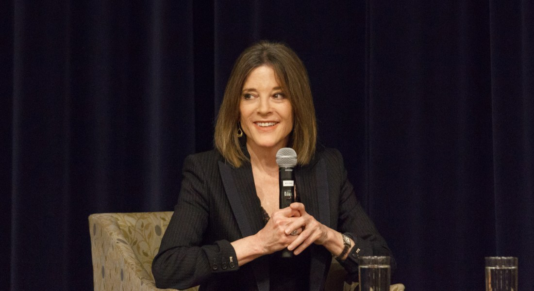 A woman in a black suit holds a microphone.