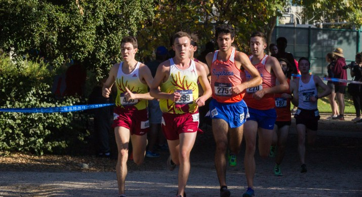 A group of four male college students in cross country attire run down a dirt track.