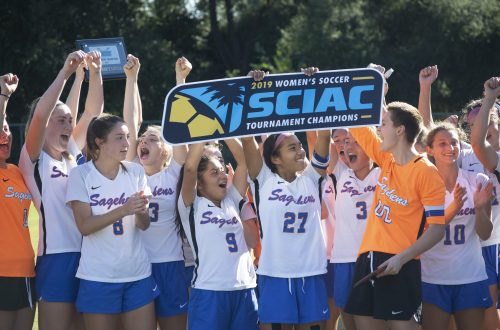 "A group of girls in soccer uniforms cheer and hold up a sign reading ""2019 Women's Soccer SCIAC Tournament Champions"