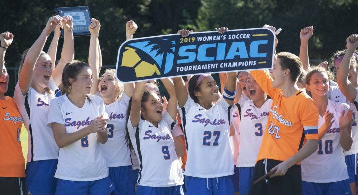 """A group of girls in soccer uniforms cheer and hold up a sign reading """"2019 Women's Soccer SCIAC Tournament Champions"""