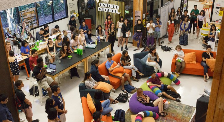 A large crowd of students gathers in a room, some sit on couches, others stand.
