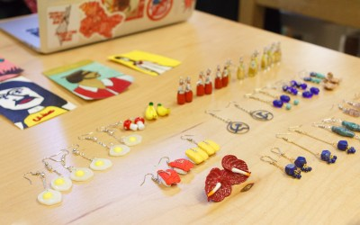 A large selection of earrings sit on a table. Examples include sushi, fried eggs, bananas and more.